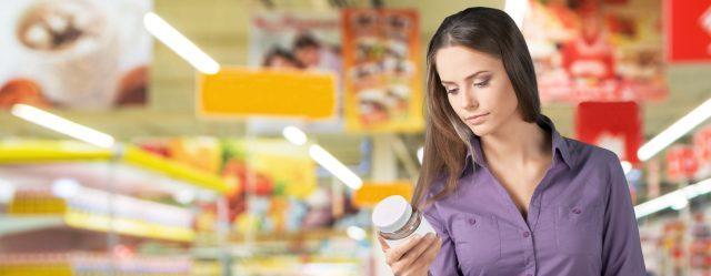 Kobieta czytająca etykiety produktów w supermarkecie